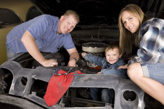 Happy family working on car Stock Images