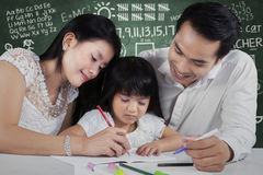 Happy family writing on book Stock Photo
