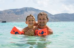 Happy family. Young beautiful father and his smiling son baby boy having fun on the beach of the sea, ocean. Positive human emotio royalty free stock photography