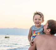 Happy family. Young beautiful father and his smiling son baby boy having fun on the beach of the sea, ocean. Positive human emotio Stock Image