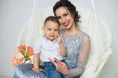 Happy family of young beautiful mother in plum dress and little positivity son, gesturing victory by fingers. Stock Photo