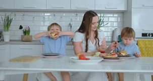 A happy family is a young beautiful mother in a white dress with two sons in blue shirts preparing a white kitchen stock video
