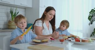 A happy family is a young beautiful mother in a white dress with two sons in blue shirts preparing a white kitchen stock footage
