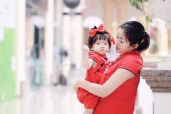Happy family young Chinese mother has fun with baby in China traditional cheongsam. Carefree childhood with parents, cute pretty mom and girl have fun together Stock Image