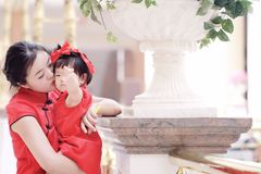 Happy family young Chinese mother has fun with baby in China traditional cheongsam. Carefree childhood with parents, cute pretty mom and girl have fun together stock images