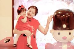 Happy family young Chinese mother has fun with baby in China traditional cheongsam. Carefree childhood with parents, cute pretty mom and girl have fun together royalty free stock image
