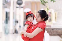 Happy family young Chinese mother has fun with baby in China traditional cheongsam. Carefree childhood with parents, cute pretty mom and girl have fun together stock photos