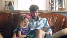 Happy family. young father and his little blond daughter are reading a story on leather sofa in the dining room. 4K stock video