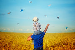 Happy family: young father with his little son walking in the w. Heat field at sunset in a warm summer day. View from a back stock images
