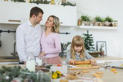 Happy family, young mother with baby, little girl making gingerbread cookie in decorated kitchen room with Christmas. Food, family, christmas, hapiness and Royalty Free Stock Photography