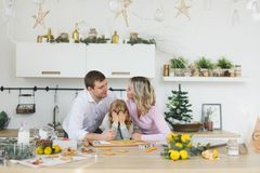 Happy family, young mother with baby, little girl making gingerbread cookie in decorated kitchen room with Christmas. Food, family, christmas, hapiness and Royalty Free Stock Images