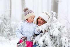 Happy family with young mother and child daughter on a winter walk outdoors. Kid toddler girl and beautiful women having fun in snow forest. Family of two Royalty Free Stock Photo