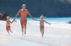 Young mother, daughter, son run by water pool along sea. Happy family - young mother, daughter, baby son hold hands, run together with splashes by water pool stock image