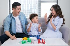 Happy family. Young mother and father playing ludo game with the. Ir son while spending time together at home Stock Images