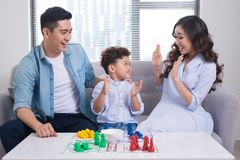 Happy family. Young mother and father playing ludo game with the. Ir son while spending time together at home Royalty Free Stock Images
