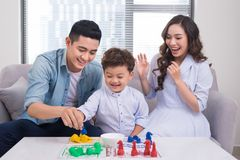 Happy family. Young mother and father playing ludo game with the. Ir son while spending time together at home Royalty Free Stock Photography
