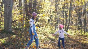 Happy young woman having fun and throwing yellow leaves at autumn forest stock footage