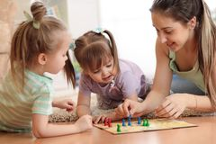 Happy family. Young mother playing ludo boardgame with her daughters while spending time together at home. stock image