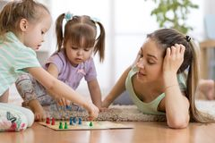 Happy family. Young mother playing ludo boardgame with her daughters while spending time together at home. royalty free stock photos