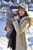 Happy family. Young mother in a winter park with her sweet baby. Boy Stock Photos