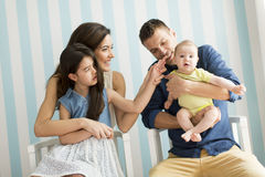 Happy family. Young family with two daughters in the room royalty free stock photography
