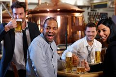 Happy fans watching TV in pub cheering Stock Photo