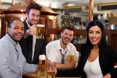Happy fans watching TV in pub cheering Stock Image