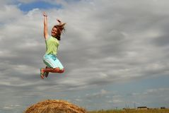 Happy Farm Girl. A pretty young woman jumps over a bale of straw with a dramatic sky overhead. (Note motion blur of feet Stock Photography
