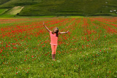 Happy farm girl. A preteen Caucasian farm girl with happy smilig facial expression stretching her arms out while standing in the blooming poppy and lentil fields Royalty Free Stock Photo