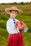 Happy farmer boy hold Organic Apples in Autumn Garden Stock Image