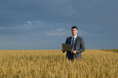 Happy farmer. buisnessmen in a wheat field. Happy farmer, businessman, standing in wheat field with his laptop Stock Images
