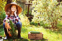 Happy farmer child girl sitting with autumn harvest in the garden Royalty Free Stock Photo