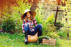 Happy farmer child girl sitting with autumn harvest in the garden. Growing fresh organic vegetables, natural healthy food and seasonal work concept Royalty Free Stock Images