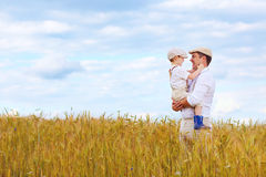 Happy farmer family on wheat field Royalty Free Stock Image
