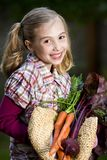 Happy Farmer Girl. A cute young girl with farm fresh vegetables Stock Photography