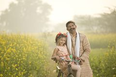 Father with daughter riding bicycle on agriculture field. Happy farmer with his daughter riding bicycle on rapeseed agriculture field stock image