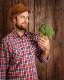 Happy farmer holding broccoli on rustic wood royalty free stock photos