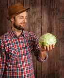 Happy farmer holding cabbage on rustic wood Royalty Free Stock Photography