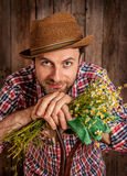 Happy farmer holding camomile flowers on rustic wood stock images