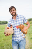 Happy farmer holding chicken and eggs Royalty Free Stock Photography
