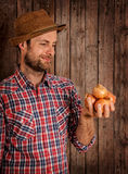 Happy farmer holding onions on rustic wood Stock Photos