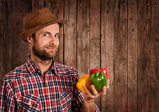 Happy farmer holding peppers on rustic wood Royalty Free Stock Images