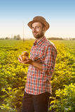 Happy farmer holding potatoes in front of field landscape Stock Photo