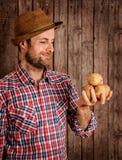 Happy farmer holding potatoes on rustic wood stock photo