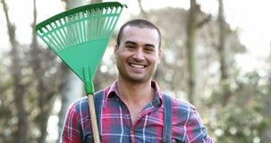 Happy farmer holding rake stock video