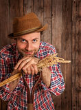 Happy farmer holding wheat bunch on rustic wood Stock Image