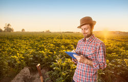 Happy farmer making notes in front of field landscape Stock Photo