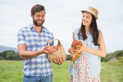 Happy farmers holding chicken and eggs Stock Photos