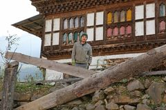 Happy Farmhand Rests in the Late Afternoon in Bhutan. Young farmhand poses for a photo in the eastern countryside of rural Bhutan Stock Photo