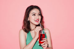 Happy fashion asian woman drinking champagne over pink backgroun Stock Photography